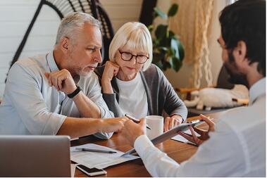 financial-advisor-explaining-paperwork-to-elderly-retired-couple-of-picture-id1264327700 (2)